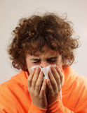 A young boy blowing his nose. A young boy is blowing his nose on a tissue Royalty Free Stock Photos