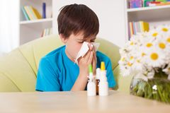 Young boy blowing nose with nazal sprays and other medication in Stock Photo