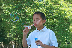 Young boy blowing soap bubbles Royalty Free Stock Photos