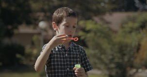 Young boy blowing soap bubbles outdoors stock footage