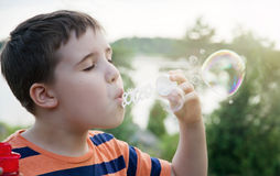 Young boy blowing soap bubbles Royalty Free Stock Photography