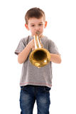 Young boy blowing into a trumpet Royalty Free Stock Image