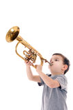 Young boy blowing into a trumpet Stock Images