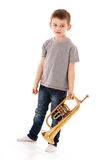 Young boy blowing into a trumpet Royalty Free Stock Photos