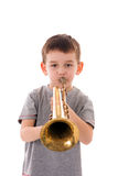 Young boy blowing into a trumpet Stock Image