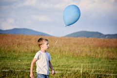 Young boy with blue balloon in meadow stock photo