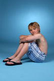 Young boy in blue plaid shorts. Against a blue background Royalty Free Stock Image