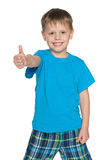 Young boy in blue shirt holds his thumb up Royalty Free Stock Photos