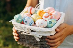 Young Boy in blue shirt holds wooden basket with hand painted eggs in hands at sunlight in spring garden. Egg hunt, spring festive stock image