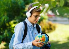Young boy in blue shirt and round glasses looks and points on globe in his hands. Education, back to school. Concept royalty free stock photos