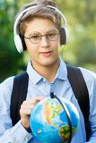 Young boy in blue shirt and round glasses looks and points on globe in his hands. Education, back to school. Concept stock image