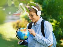 Young boy in blue shirt and round glasses looks and points on globe in his hands. Education, back to school. Concept stock photos