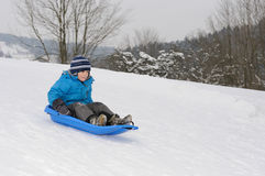 Young boy on blue sled. Riding down hill Stock Images