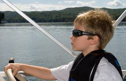 Young Boy and Boat. Young boy at the wheel of a boat trying to learn to drive royalty free stock photo