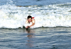 Young boy is body surfing in the waves Stock Photos