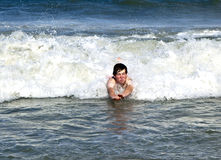 Young boy is body surfing in the waves Royalty Free Stock Image