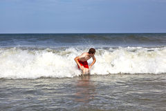 Young boy is body surfing in the waves royalty free stock photography