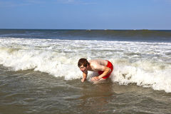 Young boy is body surfing in the waves Royalty Free Stock Photos