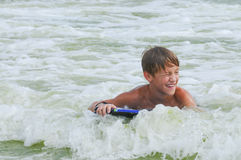 Young boy boogie boarding the waves. Happy cute kid on a boogie board in the ocean water with copy space Stock Images