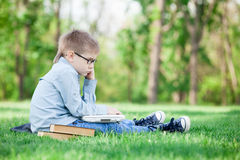 Young boy with a book and laptop computer Stock Image
