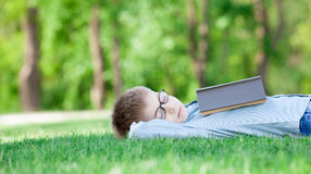 Young boy with a book slipping Stock Photography