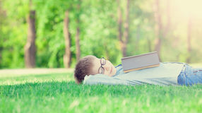 Young boy with a book slipping Royalty Free Stock Photos