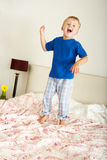 Young Boy Bouncing On Bed. Laughing Royalty Free Stock Photo