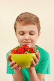 Young boy with bowl of sweet red strawberries. Young boy with a bowl of sweet red strawberries Stock Photos