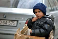 Young boy in a box in Baku, capital of Azerbaijan, next to BMW Royalty Free Stock Photography