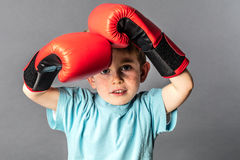 Young boy with boxing gloves protecting and defending himself Stock Photo