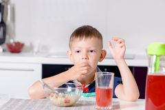 Young Boy at Breakfast Table Eating Bowl of Cereal Stock Photography