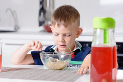 Young Boy at Breakfast Table Eating Bowl of Cereal Royalty Free Stock Photography