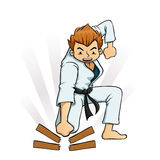Young Boy Breaking Boards in Karate Uniforms. Young boy breaking board in martial arts practice Royalty Free Stock Images