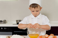 Young boy breaking fresh eggs into a bowl Stock Images