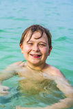 Young   boy with brown hair enjoys swimming Royalty Free Stock Image