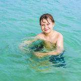 Young   boy with brown hair enjoys swimming Stock Photography