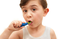 Young boy brushing teeth isolated. Isolated image of a young boy brishing his teeth with a toothbrush. The boy has brown hair, brown eyes, and is wearing a vest stock photo