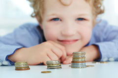 Young boy build a tower by coins. Royalty Free Stock Photography