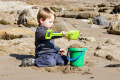 Young boy building sandcastles on beach. Boy on Filey beach building a sand castle using a bucket and spade Royalty Free Stock Photography