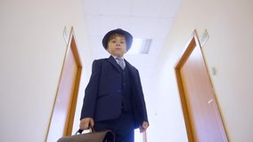 Young boy in business suit, hat standing in school corridor and looking to camera. Low angle view young businessman with. Briefcase in business office hall stock video footage