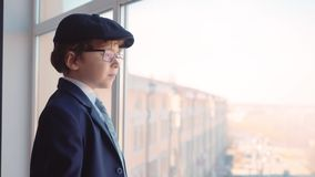 Young boy in business suit, tie and cap looks out from window in business office stock video footage