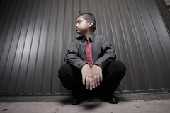 Young boy businessman squatting Royalty Free Stock Images