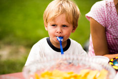Young boy with cake spoon in mouth. In the park at his birthday party Royalty Free Stock Photo