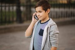 Young boy call his mom. Teenage boy use phone outside.  royalty free stock photography