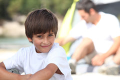 Young boy on a camping trip. With his father stock photos