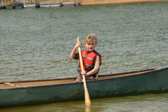 Young boy canoeing in a lake. Young boy with life vest on paddling a canoe he just launching from the bank Royalty Free Stock Photography