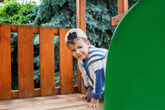 Young boy in cap climbing on playground Stock Images