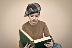 Young boy with cap reading an old book stock images
