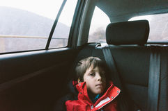 Young boy in car. Young boy in red coat sitting in backseat of car Stock Photography