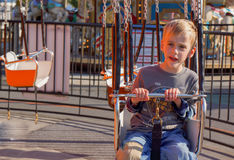 Boy on Carnival Swing. Young boy is ready for the carnival swings to start up on this first day of summer vacation stock photos